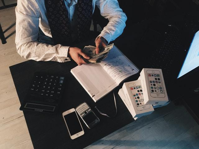 person-counting-money-with-smartphones-in-front-on-desk-210990